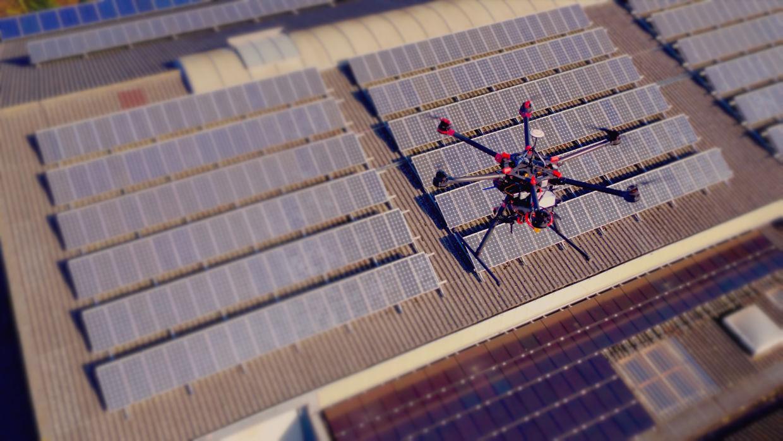 Vollbildaufnahme unserer Thermografie-Drohne mit mehreren Infarotkameras über einer Dach-Solarnlage